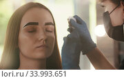 Cosmetologist wipes out the tinted color from the brow of a young woman. Стоковое видео, видеограф Константин Шишкин / Фотобанк Лори