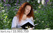 Young red-haired woman reads a book turning pages among flowers in a city park, a light wind blows through her hair. Стоковое видео, видеограф Алексей Кузнецов / Фотобанк Лори
