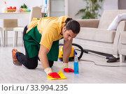 Купить «Young male contractor cleaning the house», фото № 33994235, снято 3 февраля 2020 г. (c) Elnur / Фотобанк Лори