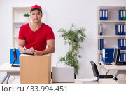 Купить «Young male courier delivering postbox to the office», фото № 33994451, снято 19 ноября 2019 г. (c) Elnur / Фотобанк Лори