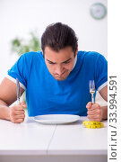 Young hungry man in dieting concept. Стоковое фото, фотограф Elnur / Фотобанк Лори