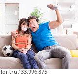 Купить «Man tying up his wife to watch sports football», фото № 33996375, снято 15 декабря 2017 г. (c) Elnur / Фотобанк Лори