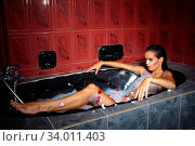 Купить «Beautiful woman relaxing in a black bathtub in red bathroom», фото № 34011403, снято 3 июля 2020 г. (c) easy Fotostock / Фотобанк Лори