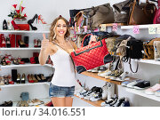 Young woman is demonstrating her choice of bag in store. Стоковое фото, фотограф Яков Филимонов / Фотобанк Лори