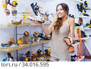 Portrait of woman looking confused with two pair of shoes. Стоковое фото, фотограф Яков Филимонов / Фотобанк Лори