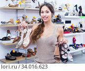 Woman customer holding many pair of shoes. Стоковое фото, фотограф Яков Филимонов / Фотобанк Лори