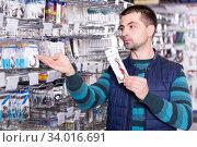young male customer choosing fishing hooks near stand in the sports shop. Стоковое фото, фотограф Яков Филимонов / Фотобанк Лори