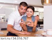 Loving couple with smartphone in kitchen. Стоковое фото, фотограф Яков Филимонов / Фотобанк Лори
