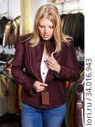 Купить «woman trying on clothes in leather outerwear shop», фото № 34016943, снято 5 сентября 2018 г. (c) Яков Филимонов / Фотобанк Лори