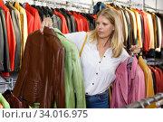 Купить «Woman choosing leather jacket», фото № 34016975, снято 5 сентября 2018 г. (c) Яков Филимонов / Фотобанк Лори