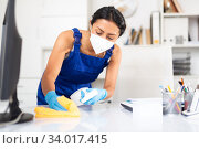 Professional cleaning woman in mask and gloves wiping desk. Стоковое фото, фотограф Яков Филимонов / Фотобанк Лори