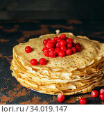 Russian pancakes with berries in front of dark background. Pancake week - the ancient Slavic festival of seeing off the winter, from which the custom of baking pancakes. Стоковое фото, фотограф Nataliia Zhekova / Фотобанк Лори