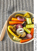 Купить «Mixed vegetable stir fry with parmesan cheese. Roasted vegetables mix on the plate with cutlery on the wicker serving mat, food above. Tender seasonal vegetables stir fry. Vegan food», фото № 34019231, снято 29 июля 2019 г. (c) Nataliia Zhekova / Фотобанк Лори