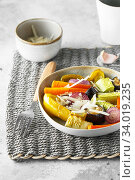 Купить «Mixed vegetable stir fry with parmesan cheese. Roasted vegetables mix on the plate with cutlery on the wicker serving mat, food above. Tender seasonal vegetables stir fry. Vegan food», фото № 34019235, снято 29 июля 2019 г. (c) Nataliia Zhekova / Фотобанк Лори
