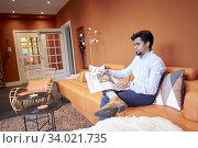 Indian man reading newspaper in lobby. Стоковое фото, фотограф Egerland Productions / age Fotostock / Фотобанк Лори
