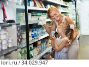 Woman and girl picking fresh dairy products in refrigerated section. Стоковое фото, фотограф Яков Филимонов / Фотобанк Лори