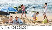 Купить «Couple relaxing on beach while their kids playing active games», фото № 34030051, снято 2 июля 2020 г. (c) Яков Филимонов / Фотобанк Лори