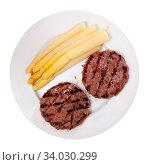 Fried cutlets with boiled asparagus on plate. Стоковое фото, фотограф Яков Филимонов / Фотобанк Лори