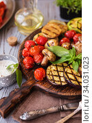 Купить «Grilled vegetables on cutting board on wooden background. Grilled vegetables (colorful bell pepper, tomatoes, onion, zucchini, eggplant) with basil», фото № 34031023, снято 20 марта 2019 г. (c) Nataliia Zhekova / Фотобанк Лори