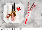 Купить «Christmas table place setting with square plate, cutlery with festive decorations gold ribbon, bauble red telephone box, star-shaped bowl with red sugar. Christmas Xmas New Year holiday backdrop», фото № 34031111, снято 12 ноября 2019 г. (c) Nataliia Zhekova / Фотобанк Лори