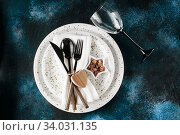 Купить «Festive table place setting. Crockery and cutlery on a dark textured background with copy space. Christmas Xmas New Year holiday», фото № 34031135, снято 12 ноября 2019 г. (c) Nataliia Zhekova / Фотобанк Лори