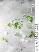 Купить «glasses of cold water with fresh mint leaves and ice cubes on grey concrete background», фото № 34031263, снято 4 июня 2019 г. (c) Nataliia Zhekova / Фотобанк Лори