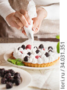 Beautiful freshly made berry meringue tart on plate. Stunning Blackberry meringue pie still life composition. Food photo. Process of making tart. Closeup hands of chef with confectionery bag. Стоковое фото, фотограф Nataliia Zhekova / Фотобанк Лори