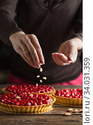 Beautiful freshly made cherry tart decorated with almond chips. Food photo. Process of making tart. Close up hands of the chef sprinkling cake with almond chips at pastry shop kitchen. Стоковое фото, фотограф Nataliia Zhekova / Фотобанк Лори