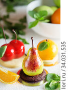 Купить «Mousse dessert in the shape of a pear fruit, orange fruit and cherry.», фото № 34031535, снято 4 февраля 2019 г. (c) Nataliia Zhekova / Фотобанк Лори