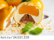 Купить «Mousse dessert with orange zest and mint in the shape of an orange fruit.», фото № 34031539, снято 4 февраля 2019 г. (c) Nataliia Zhekova / Фотобанк Лори