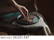 Chocolate cookies on the plate. Dark and Moody, Mystic Light food photography. Children's hand takes a cookie. Стоковое фото, фотограф Nataliia Zhekova / Фотобанк Лори