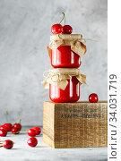 Купить «Homemade cherry jam in glass jar on the wooden box on the gray background. Two jars of cherry jam on wood with cherries in the back. Food photography. Seasonal cooking», фото № 34031719, снято 10 июня 2019 г. (c) Nataliia Zhekova / Фотобанк Лори
