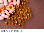 Pink tablets and fish oil on a brown background, top view. Стоковое фото, фотограф Катерина Белякина / Фотобанк Лори