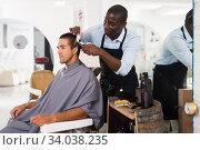 Man getting haircutting by African barber. Стоковое фото, фотограф Яков Филимонов / Фотобанк Лори