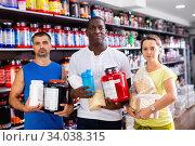 Купить «Smiling young woman and two athletic men holding jars of sports food supplements in shop interior», фото № 34038315, снято 13 июля 2020 г. (c) Яков Филимонов / Фотобанк Лори