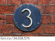 3 Digit on Dark Metal Background on red brick wall. Стоковое фото, фотограф Nataliia Zhekova / Фотобанк Лори