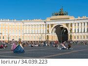 Люди сидят на булыжной мостовой Дворцовой площади. Санкт-Петербург (2020 год). Редакционное фото, фотограф Румянцева Наталия / Фотобанк Лори