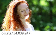 Portrait of a cute red-haired  young adult woman with a sunny spot on her face on the natural background of the city park. Стоковое видео, видеограф Алексей Кузнецов / Фотобанк Лори