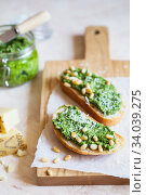 Toasts with traditional Italian basil pesto sauce on a light grey stone table. Green pesto with nuts and parmesan. Стоковое фото, фотограф Nataliia Zhekova / Фотобанк Лори