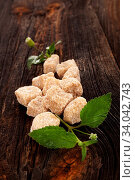 Купить «Refined Brown Cane Sugar cube with aztec sweet herb leaves on wooden table from above. Natural sugar concept.», фото № 34042743, снято 12 июля 2020 г. (c) easy Fotostock / Фотобанк Лори