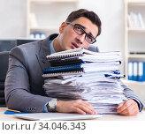 Overloaded with work employee under paperwork burden. Стоковое фото, фотограф Elnur / Фотобанк Лори