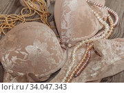 Sexy lace lingerie and pearls on a wooden board. Стоковое фото, фотограф Nataliia Zhekova / Фотобанк Лори