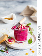 Beetroot dipping sauce in the glass decorated with almond petals and mangold leaves. Vegan recipes, plant-based dishes. Стоковое фото, фотограф Nataliia Zhekova / Фотобанк Лори