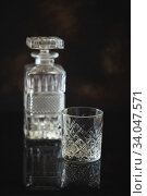 Купить «Empty Glass for whiskey or bourbon with and a crystal square decanter on the black reflective surface», фото № 34047571, снято 13 мая 2020 г. (c) Nataliia Zhekova / Фотобанк Лори