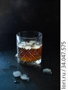 Glass of whiskey or bourbon with ice on black stone table. Glass of whiskey with ice and a square decanter. Стоковое фото, фотограф Nataliia Zhekova / Фотобанк Лори