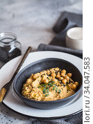 Купить «Chickpeas hummus in the black bowl decorated with sesame seeds and chickpeas greens. Vegan recipes, plant-based dishes. Green living concept. Organic food. Vegetarian», фото № 34047583, снято 2 марта 2020 г. (c) Nataliia Zhekova / Фотобанк Лори