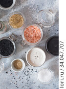 Купить «Mix of different salt types on grey concrete background. Sea salts, black and pink Himalayan salt crystals, powder. collection of different types of salt. Top view flat lay. Different Sea salts», фото № 34047707, снято 11 февраля 2020 г. (c) Nataliia Zhekova / Фотобанк Лори