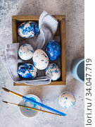 Купить «Dyed Easter eggs. Сlassic blue Easter eggs on the grey background. Blue speckled easter eggs with paint and brushes. Decorating eggs, preparing for Easter», фото № 34047719, снято 27 февраля 2020 г. (c) Nataliia Zhekova / Фотобанк Лори