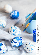 Купить «Dyed Easter eggs. Сlassic blue Easter eggs on the grey background. Blue speckled easter eggs with paint and brushes. Decorating eggs, preparing for Easter», фото № 34047727, снято 27 февраля 2020 г. (c) Nataliia Zhekova / Фотобанк Лори