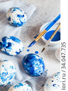 Купить «Dyed Easter eggs. Сlassic blue Easter eggs on the grey background. Blue speckled easter eggs with paint and brushes. Decorating eggs, preparing for Easter», фото № 34047735, снято 27 февраля 2020 г. (c) Nataliia Zhekova / Фотобанк Лори